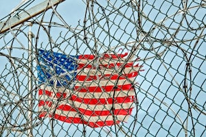 US flag through a fence